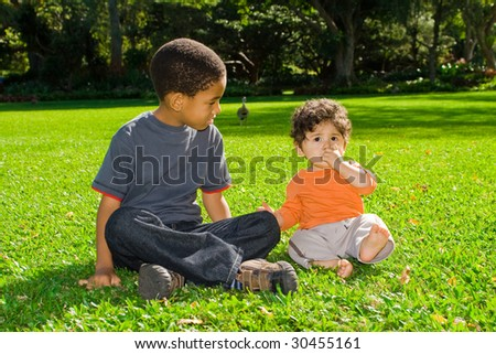 two boys sitting on green grass outdoors - stock photo