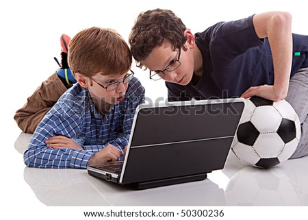two boys sitting on the floor playing computer, one holding a football, isolated on white background - stock photo