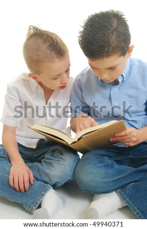Two boys sitting reading book isolated on white. - stock photo