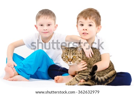 Two boys sitting together with a cat Scottish Straight isolated on white background - stock photo
