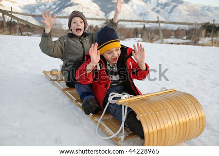 two boys sledding down a hill on a toboggan with excited expressions - stock photo