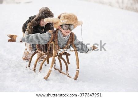 Two boys sledding with mountain warm winter day - stock photo