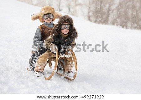 Two boys sledding with mountain warm winter day