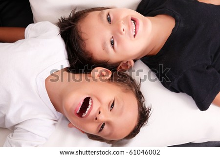 Two boys smiling and looking at the camera over white and black background