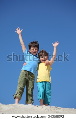 Two boys stand on sand and  lifted hands in greeting