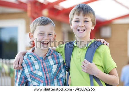 Two Boys Standing Outside School With Book Bags - stock photo