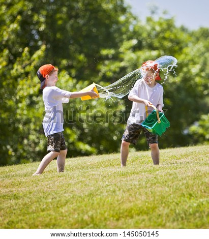 Two boys throwing buckets of water at eachother