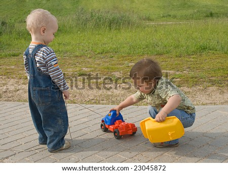 Two boys trying to repair a toy truck - stock photo