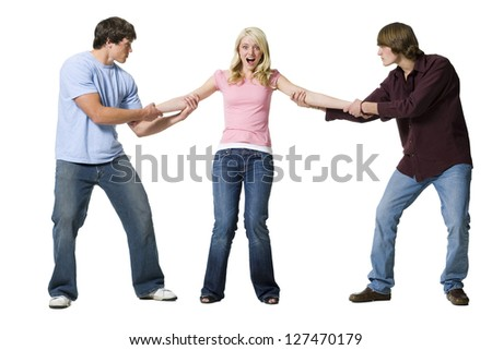 Two boys tugging at arms of girl
