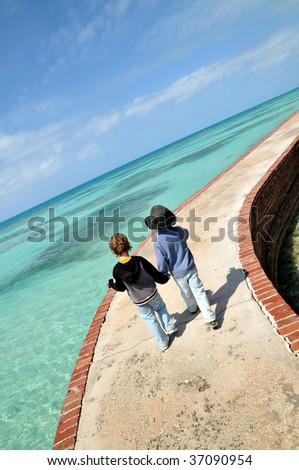 Two boys walking on a pier in tropical waters - stock photo