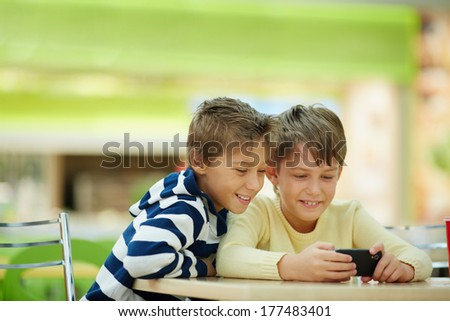 Two boys watching smartphone photos - stock photo