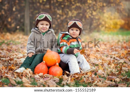 Two boys with a suitcase and pumpkins
