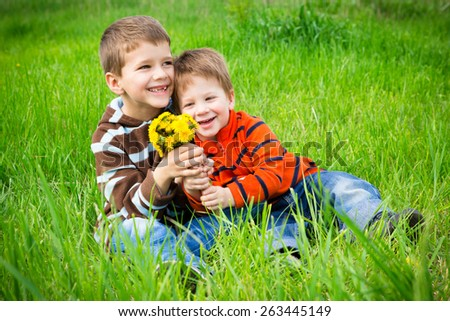 Two boys with bouquet of dandelions sitting on green meadow - stock photo