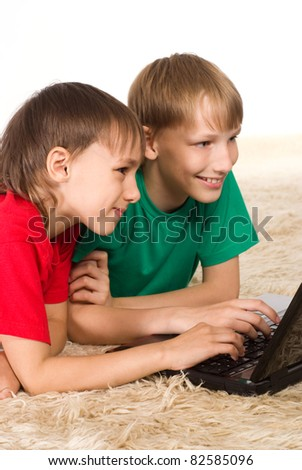 two boys with laptop lying on a carpet