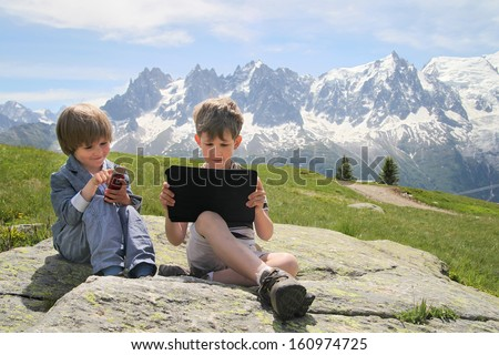 Two boys with tablet PC in Alps - stock photo
