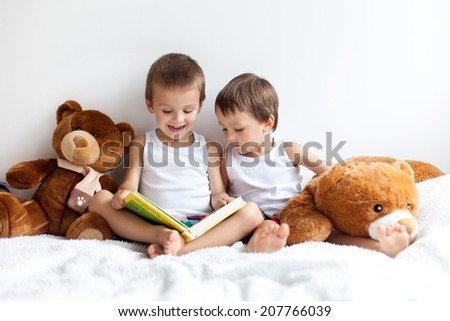 Two boys with teddy bears around, reading a book, educating themselves