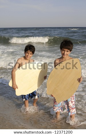 Two boys with their skimboards at the beach. - stock photo