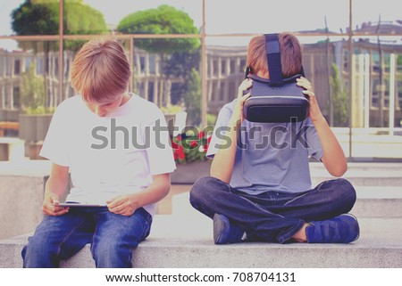 Two boys with virtual reality goggles and tablet computer in the city