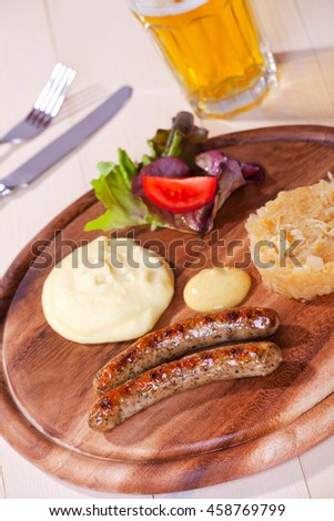 two bratwurst sausages on a wooden plate  - stock photo