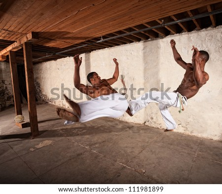 Two Brazilian martial artists performing techniques in mid-air - stock photo