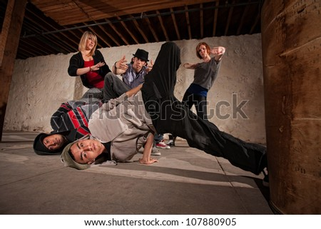 Two break dancers landing from a headspin - stock photo