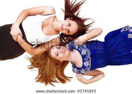 Two bretty woman with long hair lying head on head on the floor, one blond, one brunette and there hair spread out, over white. - stock photo