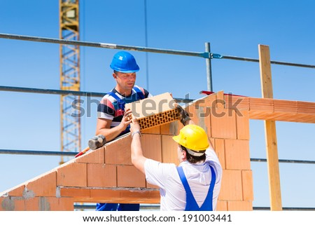 Two Bricklayer or builder or worker build or bricklaying or laying a stone or brick wall on construction or building site - stock photo