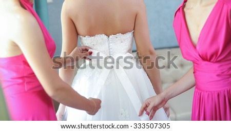 Two bride-maids in fuchsia dresses bustling the wedding dress. Bride-maids hands ribbon making on the back of bride white dress. Wedding preparation. - stock photo