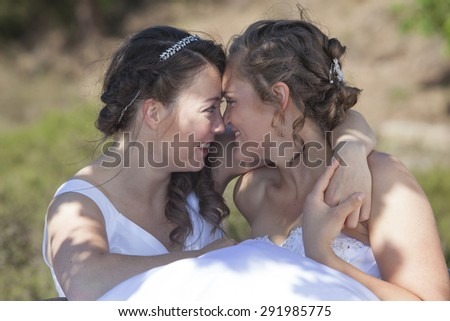 two brides smile and embrace in nature surroundings on sunny day - stock photo