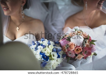 Two brides with the bouquets in the wedding car