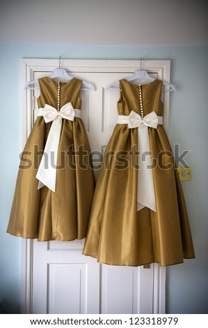 two bridesmaids dresses on hangers before a wedding - stock photo
