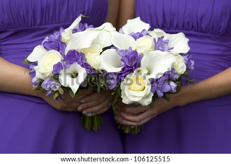 two bridesmaids in purple with wedding bouquet - stock photo