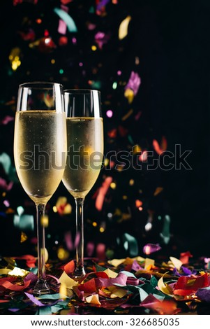 Two bright icy champagne glasses and confetti falling - stock photo