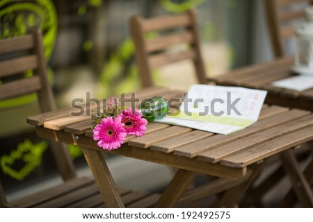 Two bright pink gerbera daisy flowers in overturned vase and menu on the wooden table, failed romantic date scene in the street city cafe, Berlin, Germany - stock photo