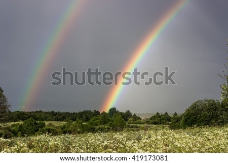 Two bright rainbow over green field in summer. - stock photo
