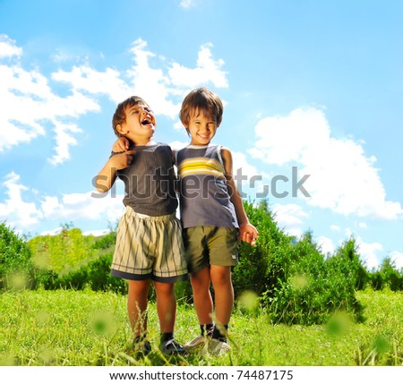 Two brother huging each other outdoor, smiling and laughing - stock photo