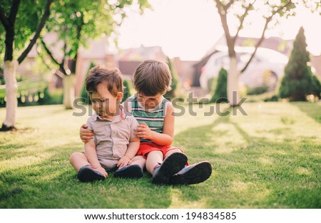 Two brothers, a baby and a toddler, sitting together on grass - stock photo