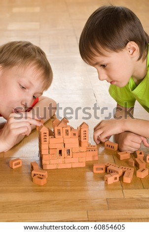 Two brothers are building  of a toy castle - stock photo