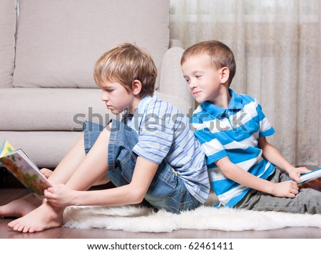 Two brothers are reading books in the room. - stock photo