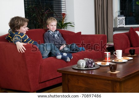 Two brothers are sitting on a couch in the livingroom - stock photo