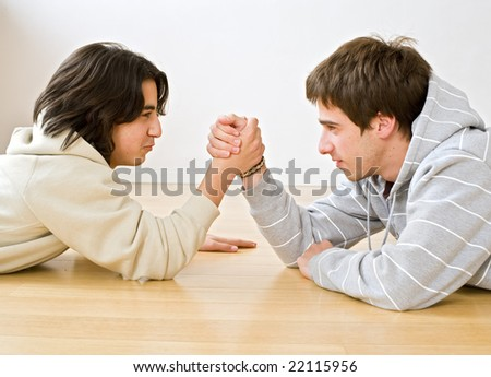 two brothers arm wrestling on the floor