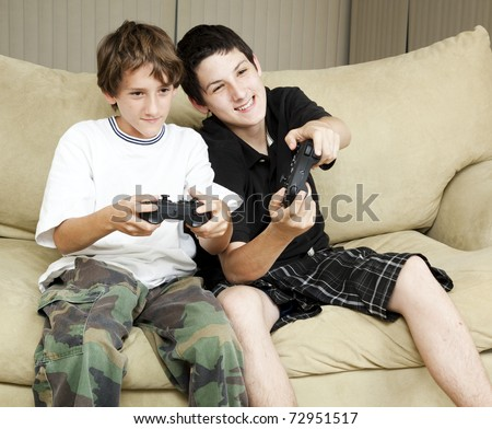Two brothers at home playing video games together. - stock photo
