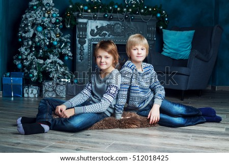 two brothers at home with Christmas tree and presents