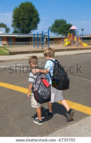 two brothers cross the street at a cross walk on their way to school - stock photo