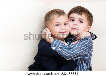 Two brothers cuddling on the couch - stock photo