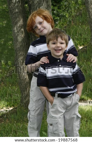 Two brothers dressed nicely smiling for the camera. - stock photo