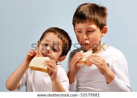 Two brothers eating toast bread sandwiches - stock photo