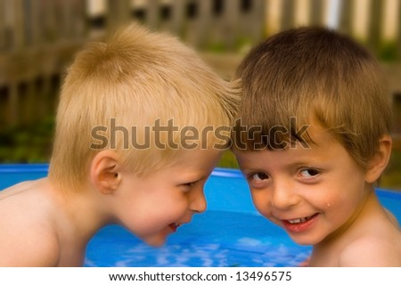 Two brothers enjoying summer in their paddling pool. - stock photo