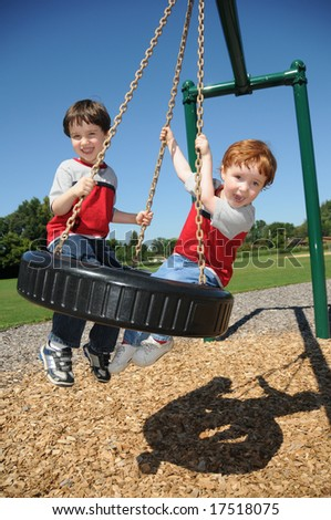 Two brothers have fun swinging on a tire swing at a neighborhood park. - stock photo
