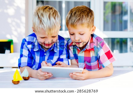 Two brothers having fun playing on digital tablet outside the home - stock photo